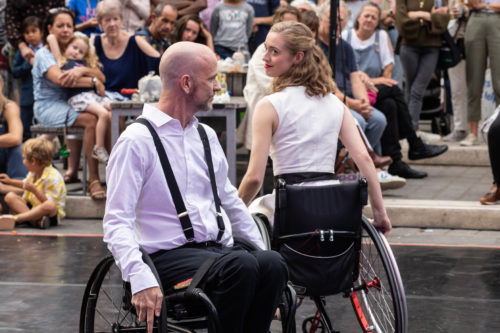 Male and female wheelchair dancer look at each other over their shoulders