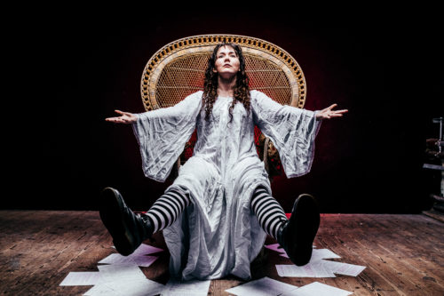 D sits in a large wicker sun chair with her arms spread open wide and her legs pointing out in front of her. She is wearing a long white flowing dress and stripy black-and-white tights. Her dark curly hair hangs down around her face.