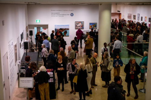 Large crowd at an art exhibition opening