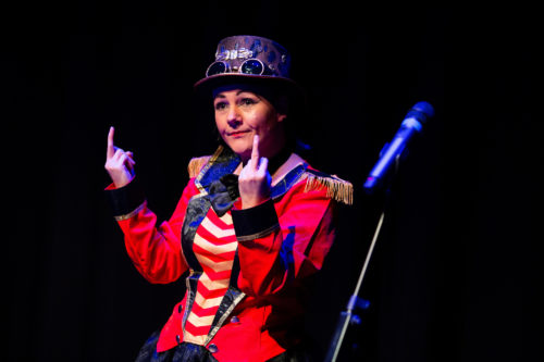 a performer dressed in a bright red circus ringmaster outfit raises two middle fingers
