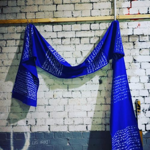 A five meter long royal blue calico with stripes made up of white text displayed on a white brick wall