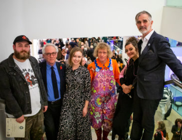 A group of people pose for a picture at an exhibition launch event