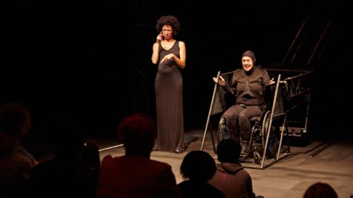 Jess Thom, on stage, dressed all in black and sitting in her wheelchair, looking animated. A BSL interpreter is signing next to her. Image by James Lyndsay.