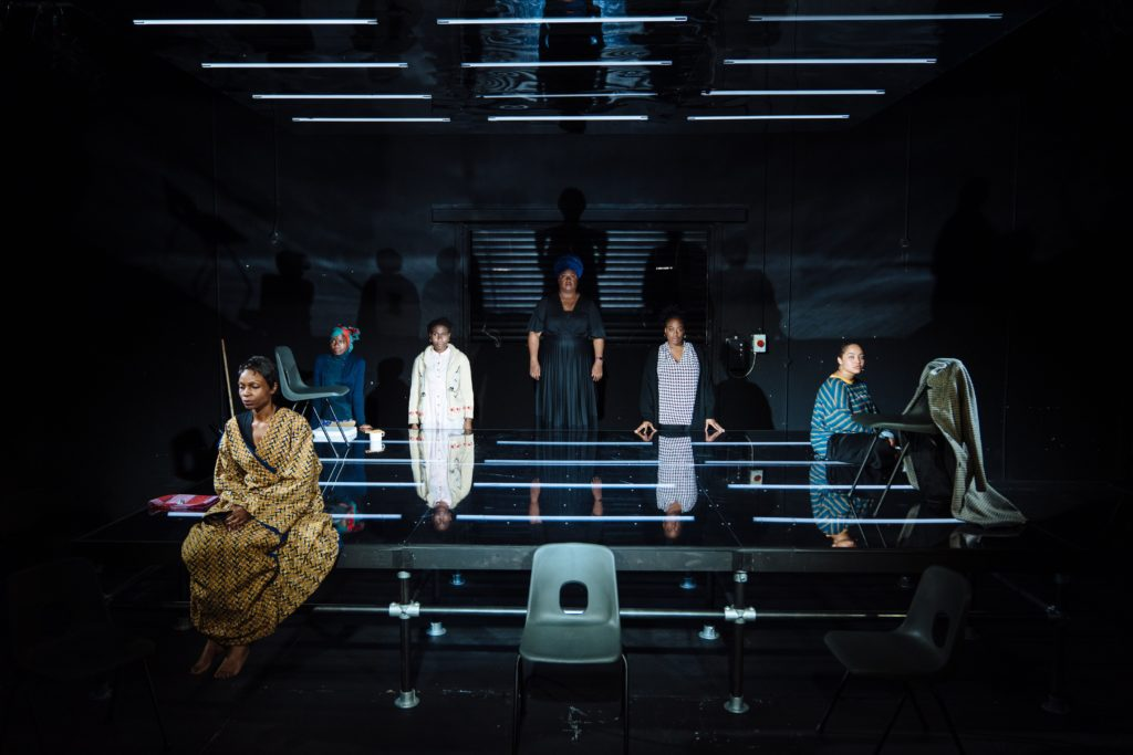 All-black and all-demale cast standing around an illuminated black stage