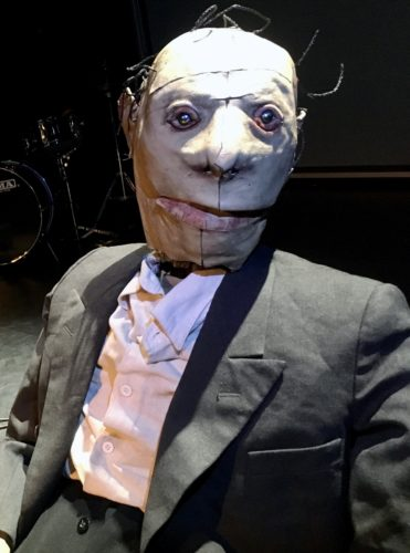An image of a slumped puppet with a deformed face in a rehearsal room with a drum in the background