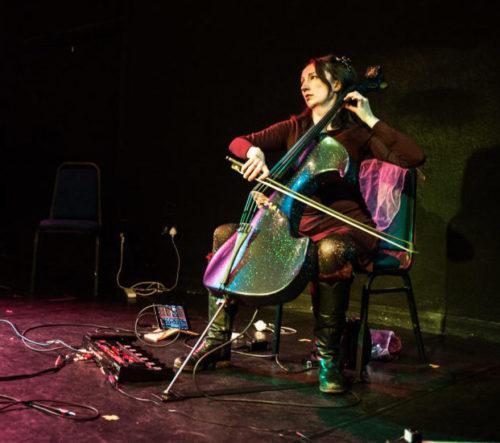 A white woman playing a black cello