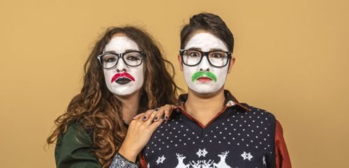 Yellow background, two women wearing ugly Christmas jumpers. Their faces are covered in white paint and green/red mustaches.