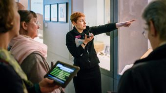 A Wellcome Collection Visitor Experience Assistant points at a cabinet display while speaking into a phone. Audience members around her are holding a screen displaying speech-to-text.