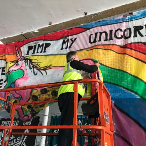 photo of man fixing a banner