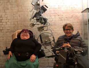 Two female wheelchair users in front of sculpture