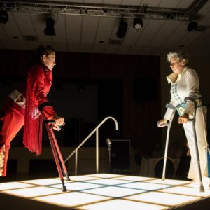 Two dancers with crutches face off on an illuminate stage, one wears a red Elvish costume, the other a white one