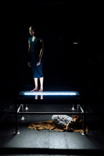 Young girl crouched underneath a stage while a woman stands on top of it above her