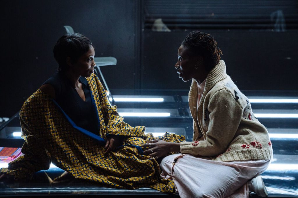 OTwo black actresses sit on the edge of a stage, on comforting the other