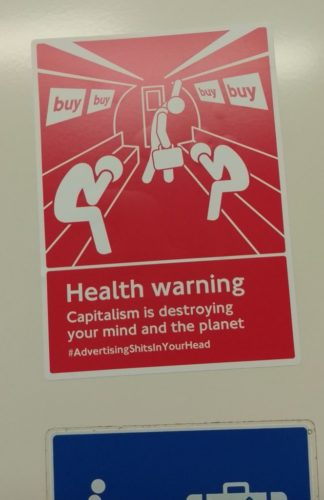 photo of red sticker on tube carriage, in the style of official tube safety stickers. It shows white slumped stick figures on the tube with their heads in their hands.The caption reads Health warning. Capitialism is destroying your mind and the planet #AdvertisingShitsInYourHead