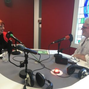 A man and woman in a radio studio, laughing