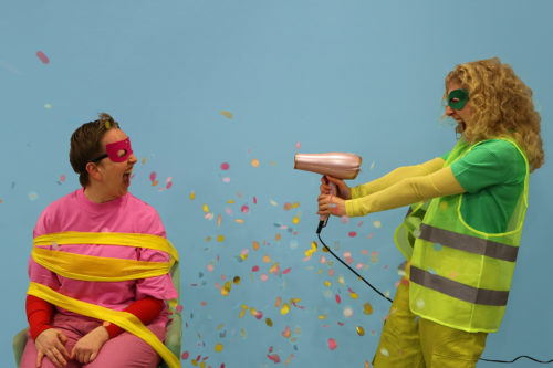 Two women wearing high-vis, one pointing a hairdryer at the other shooting out confetti