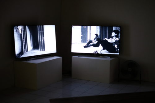 Two TV monitors are in a gallery, on plinths and at right angles to each other. The screen on the right shows two men sitting against a wall, the screen on the left shows an open door.