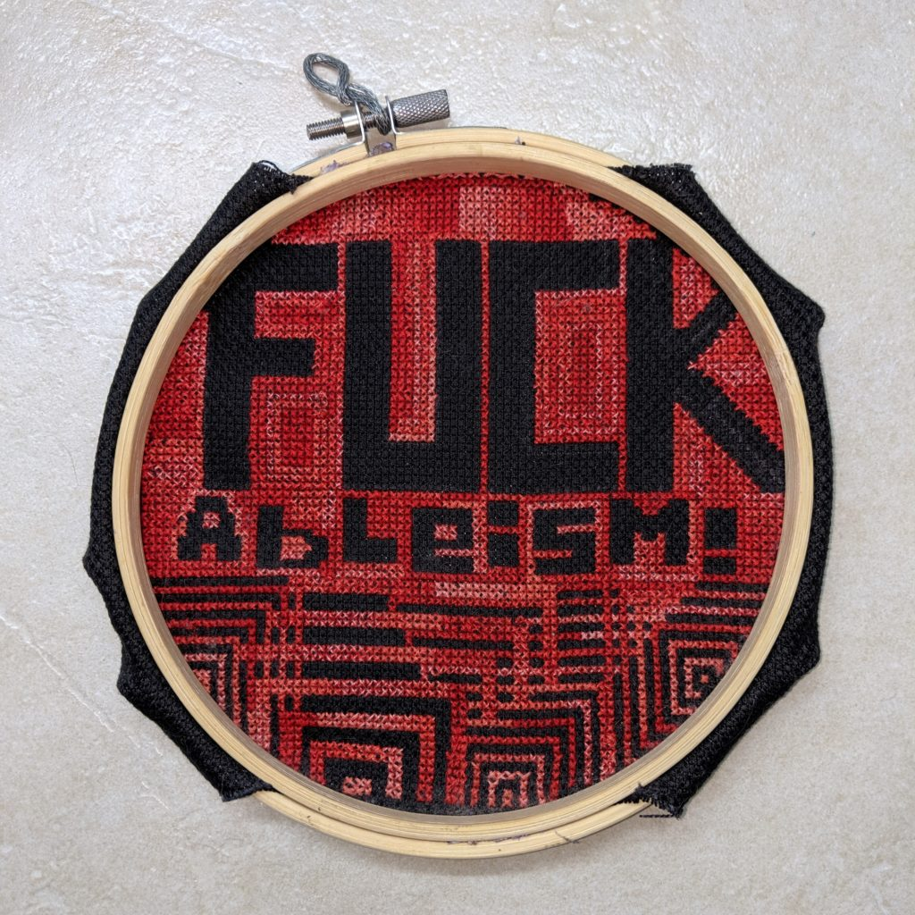 Corss stitch which has the words Fuck Ableism