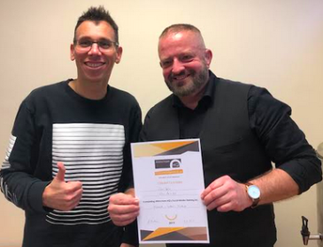 Two men giving thumbs up, one of them is holding a certificate