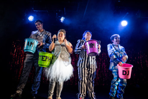 four performers in glitzy costumes pose with brightly coloured buckets, under bright stage lights
