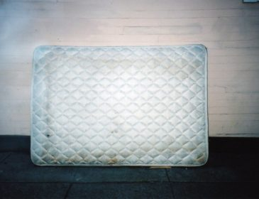 A mattress propped up against a wall