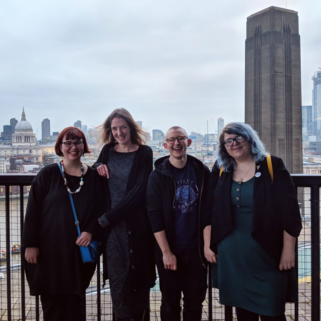 Four artists stand on a balcony with a view of London in the background.