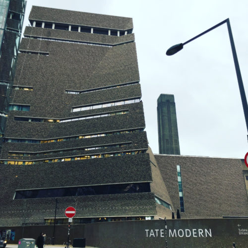 A large brown tower with irregular windows and the words Tate Modern on a wall at the bottom