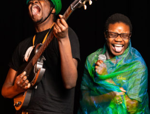 A photo of two people wearing colourful fabric, playing instruments and laughing.