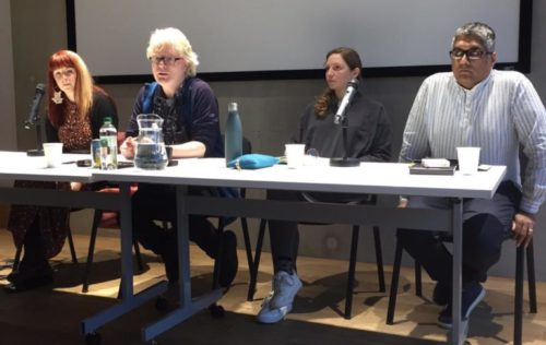 Four people sit behind a table as a panel debate