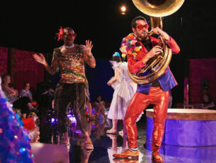 A person dressed in colourful clothing plays a sousaphone, while another person dressed in sparkly clothes dances as audiences watch them.