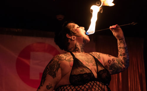 A person with tattoos about to eat a fire-eating stick that's lit with a bright flame.