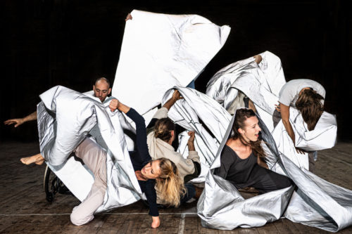 Dancers with animated faces entangled in shiny, silver material