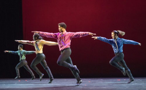 4 men dancing with arms outstretched. They are dressed in bright coloured shirts, colourful ties and black trousers.