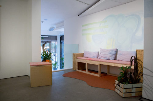 Gallery wall with mural and seat with cushions