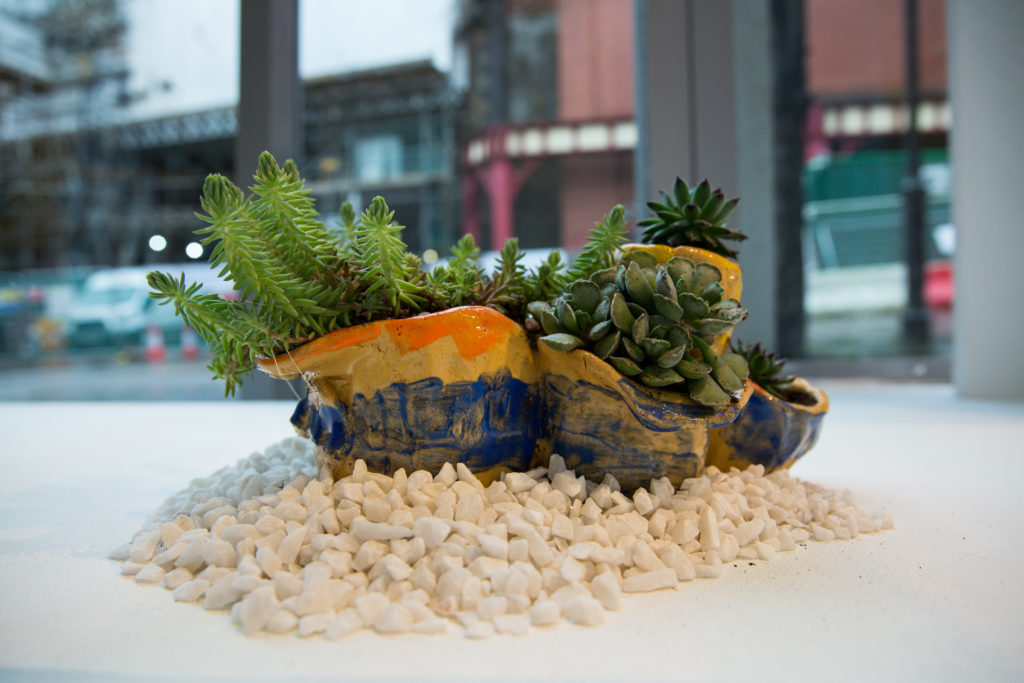 Ceramic artwork with plant inside it
