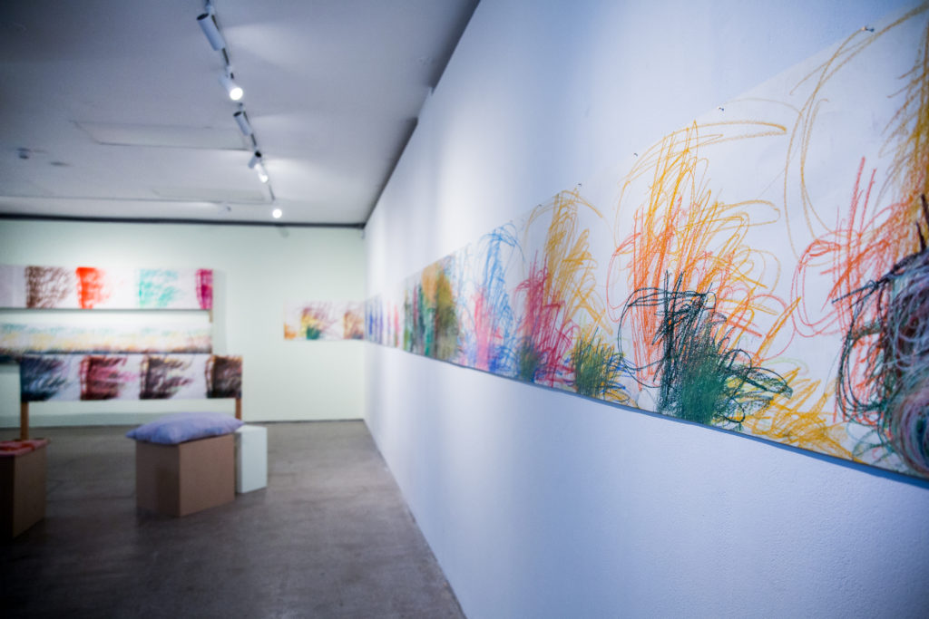 Series of colourful, scratchy artworks on a gallery wall