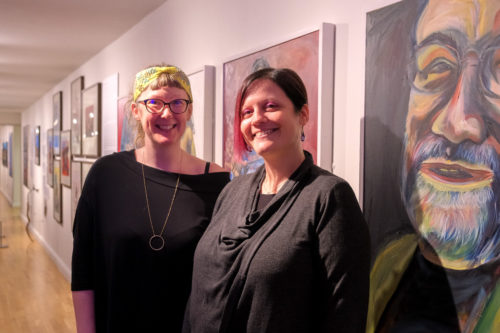 Two white women smile at camera in front of portraits