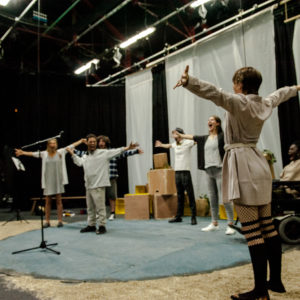Theatre workshop in which all participants have arms outstretched