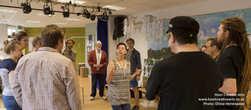 A photo of a creative session. A group of people stand round in a circle with a woman stood in the middle of them.
