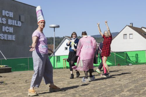 A group of people standing on a roof top. The person in the foreground wears a tall hat, pink tshirt, grey trouser and brown chunky shoes. The group in the background seem to be dancing.
