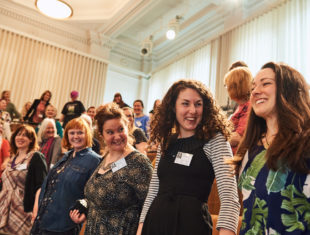 A group of women stood in a conference hall holding hands laughing and smiling.