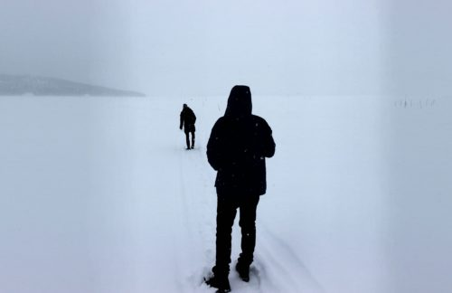 Two figures on a frozen river in the snow with their backs to us. One is walking away from the other into the distance. The atmosphere is cold - physically and emotional separateness is suggested