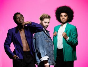 3 drag kings stand in front of a pink background. On the left, a black drag king with short hair and a moustache wearing an unbuttoned purple jacket and black trousers. In the middle a white drag with swept back short light hair and a beard wearing a blue baggy denim jacket. On the right stands a black drag king with an afro, moustache and goatee wearing a green jacket, white shirt and black trousers.
