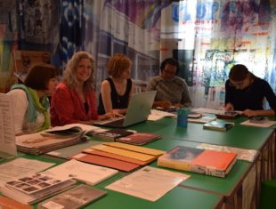 A group of women sit round a large green table. The table is covered in documents folders and books. Some of the women are using laptops.