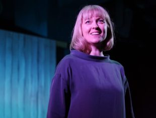 White woman shoulder-length blone hair and blue jumper smiling