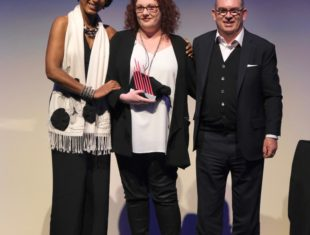 Woman with red hair being presented an award by man and woman standing either side of her