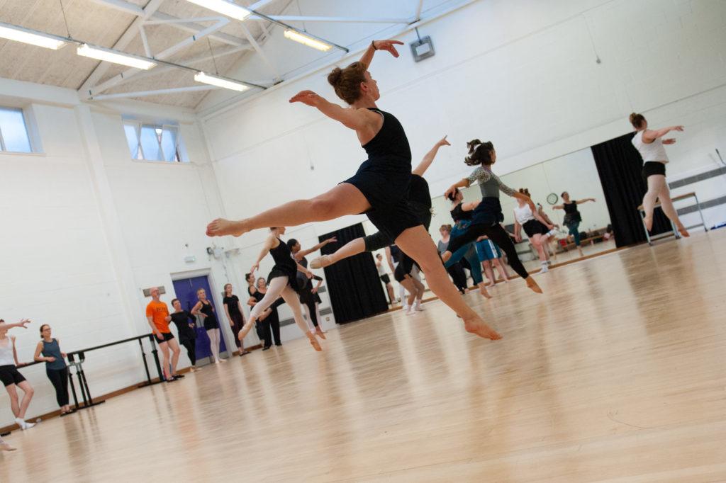 Mixed ballet workshop, dancers jump in mid air