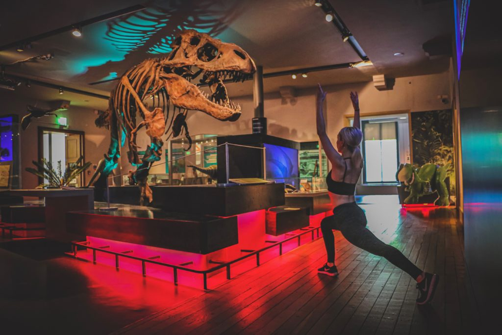 Woman doing yoga pose in front of museum T-rex exhibit