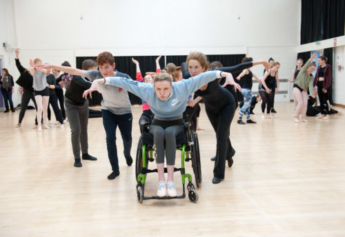 Dance workshop, female wheelchair dance comes towards the camera with arms outstretched, other people behind her also have arms outstretched