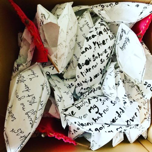 A close up photo of a large number or origami boats in a packing box. The boats feature black text on white paper in two kinds of handwriting. The text can't be read. There is also three bands of red the tops of sails from larger boats which are peeping out from underneath the top layer of boats.